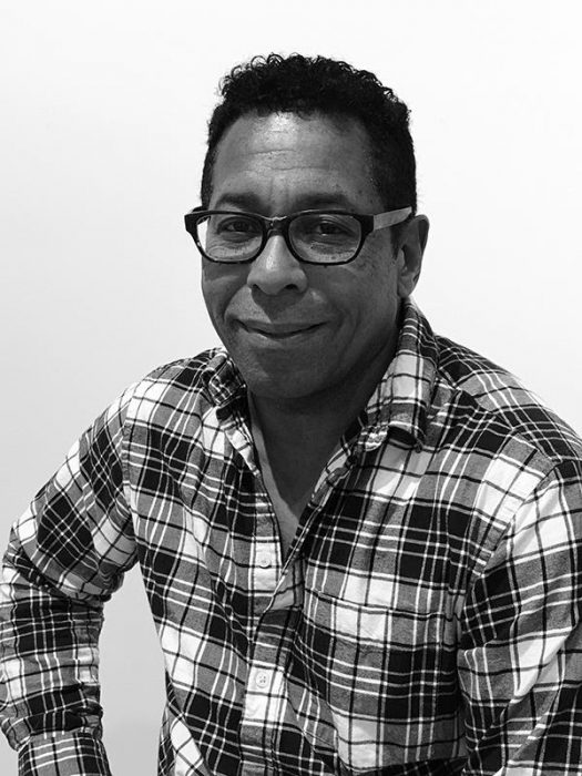 Black and white medium shot of a black man smiling and wearing a plaid shirt.