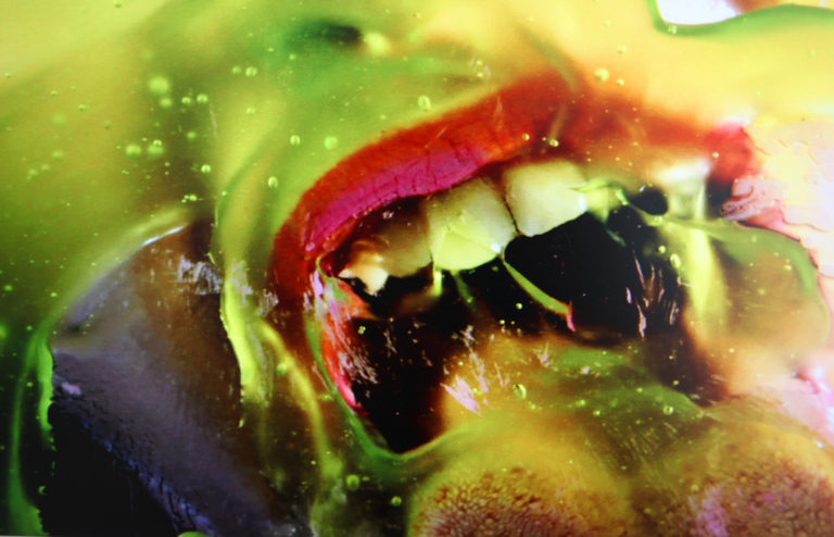 Close up image of a woman's open mouth licking at green liquid