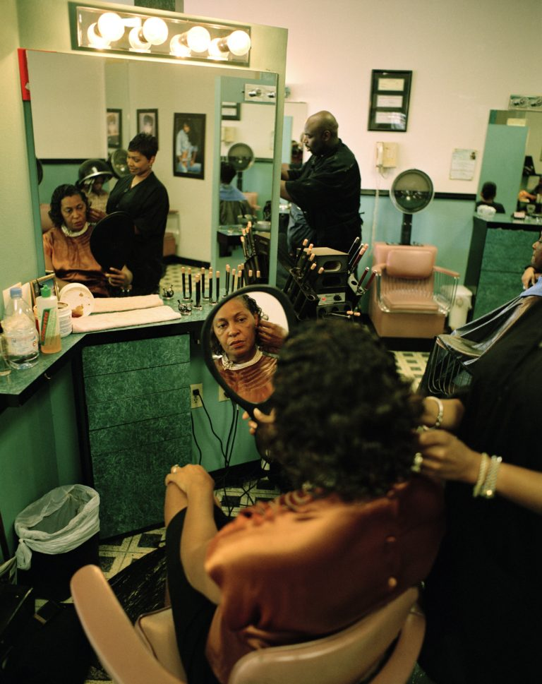 Black woman sitting in a chair at the hair salon, looking at her reflection in a hand mirror