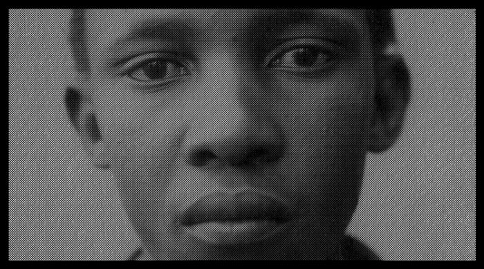 Black and white up close photograph of an African American boy