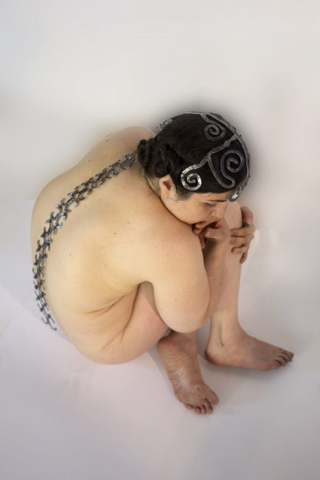 A naked woman sitting on the ground seen from above, wearing a metal spine-like object that goes from her head to her lower back