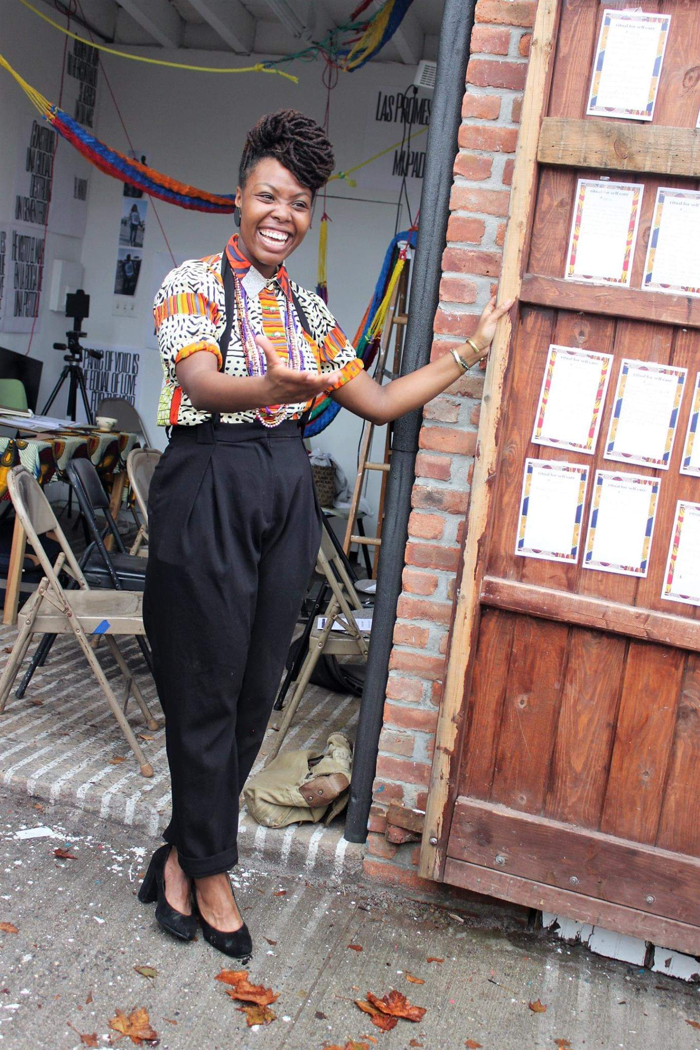 Smiling black woman standing outside near an open wood door.