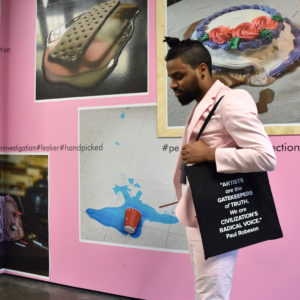 Photo of a young black man wearing a pink suit and a black tote bag against a pink wall