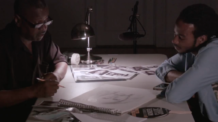 Two men sitting at a table looking at sketch drawings