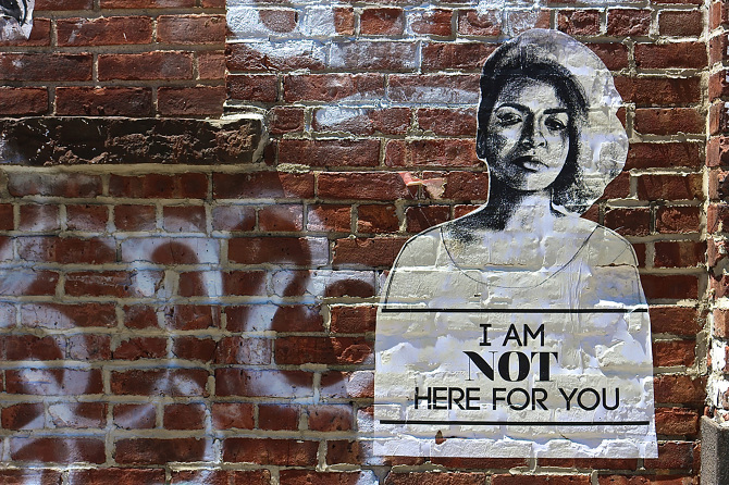 "Photo of woman on a brick wall with graffiti saying ""I am not here for you"""