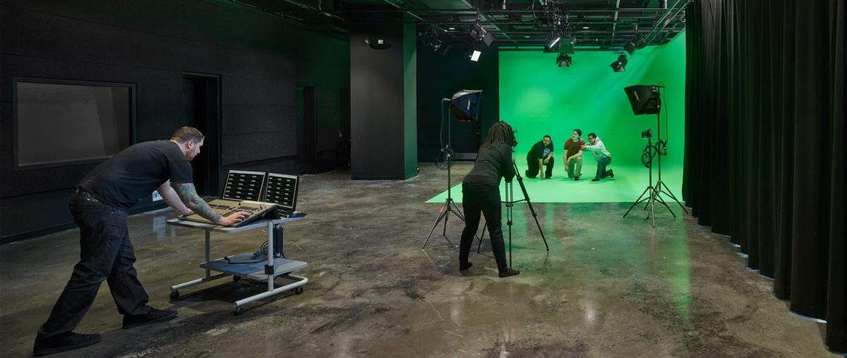 Two people film a group of three posing in front of a green screen.