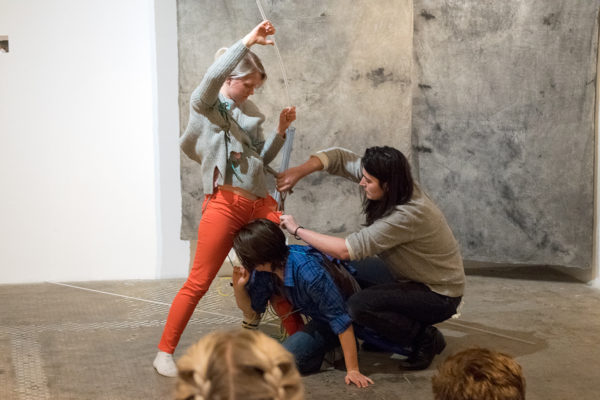 Three women work to make a sculpture out of objects and themselves