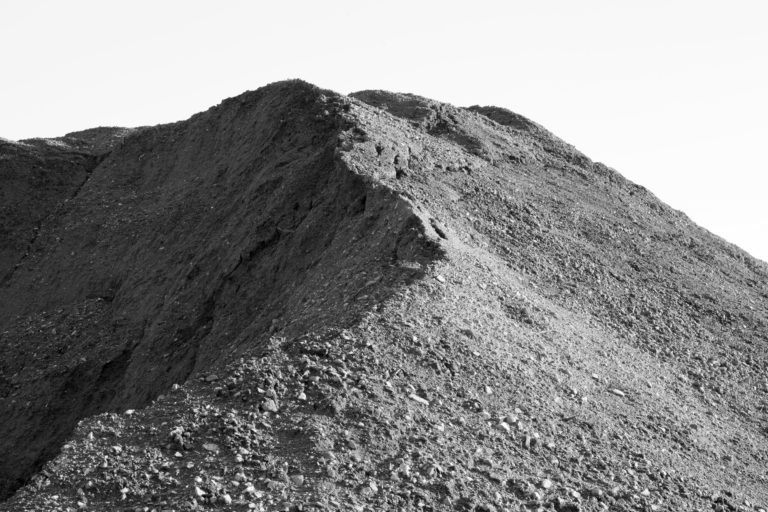 Black and white photograph of a mound of dirt