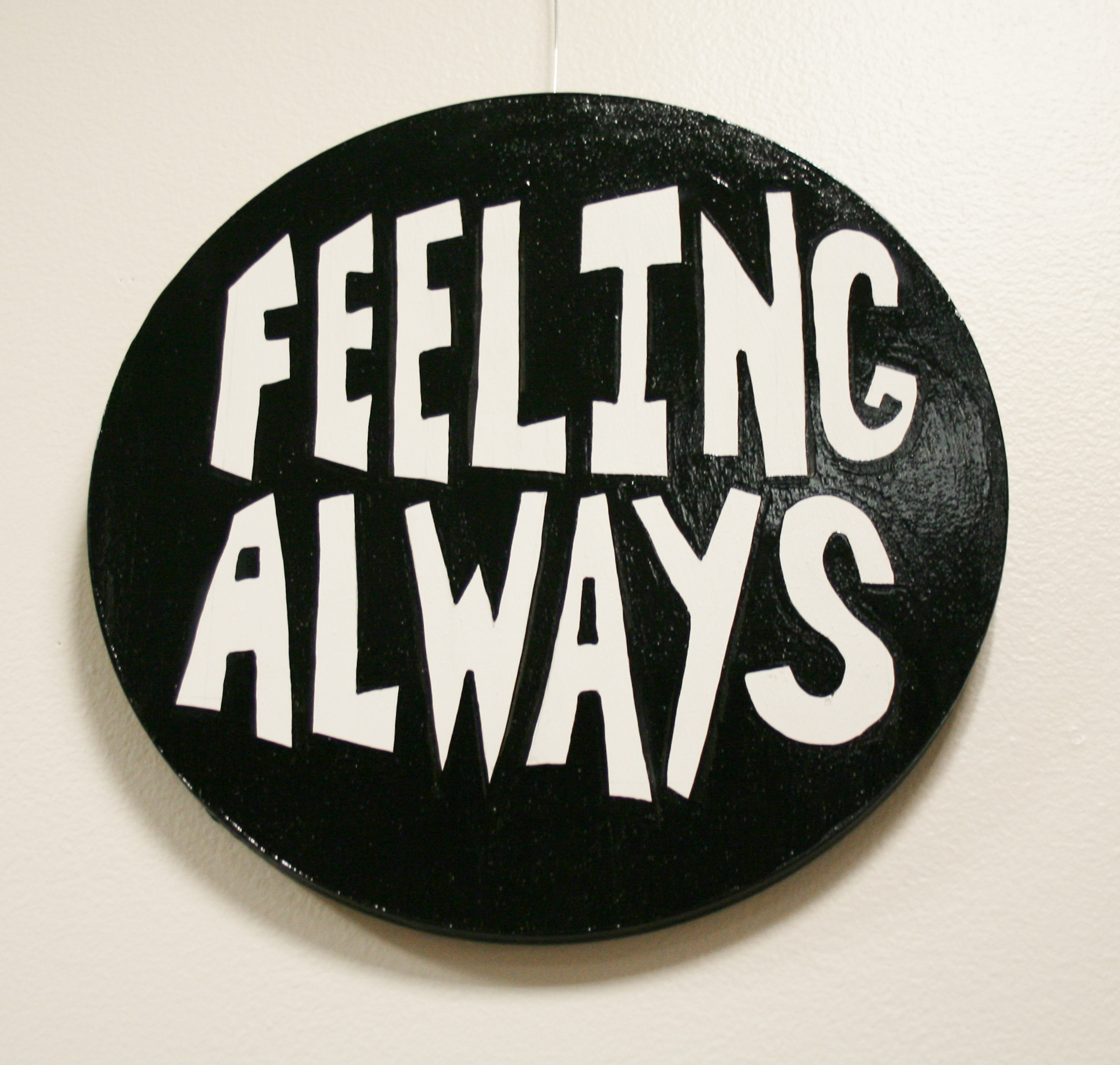 "Round wall work reading, ""Feeling always."" in white letters against a black background"