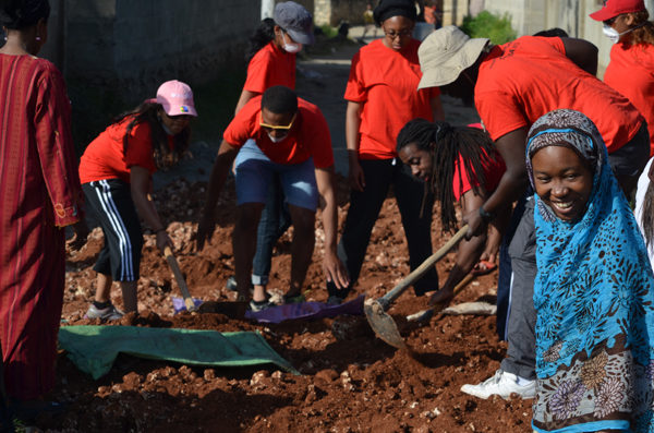 A group of students in red t-shirts digging a hole