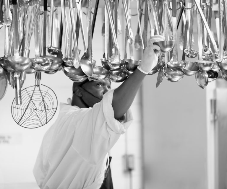 A man in chefs whites reaches up to grab a ladle hung from a rack above his head