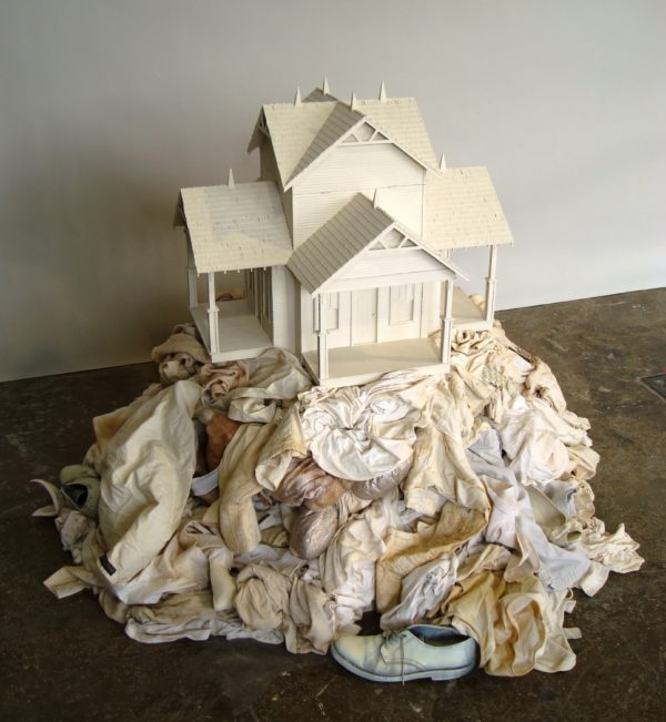 A white doll house resting a top of a pile of white clothing