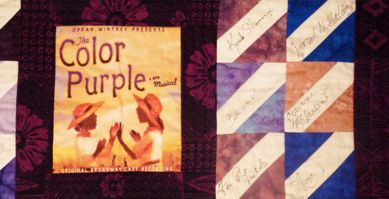"""A quilt decorated with the cover of the book, """"The Color Purple"""""""
