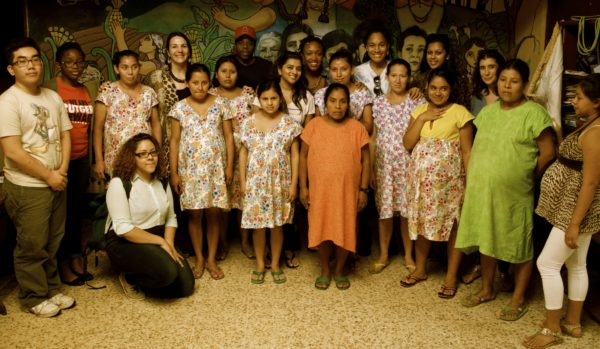 A group of primarily women of various ages and ethnicities standing in a half circle, looking at the camera