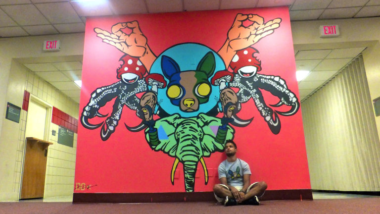 A young man sitting in front of a wall mural