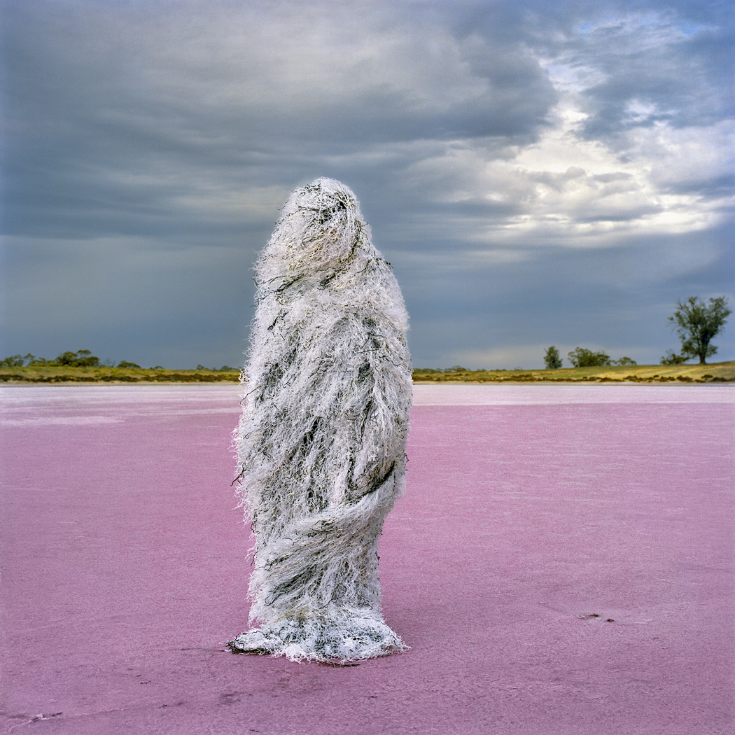Person wearing a ghillie suit, standing in a stark landscape