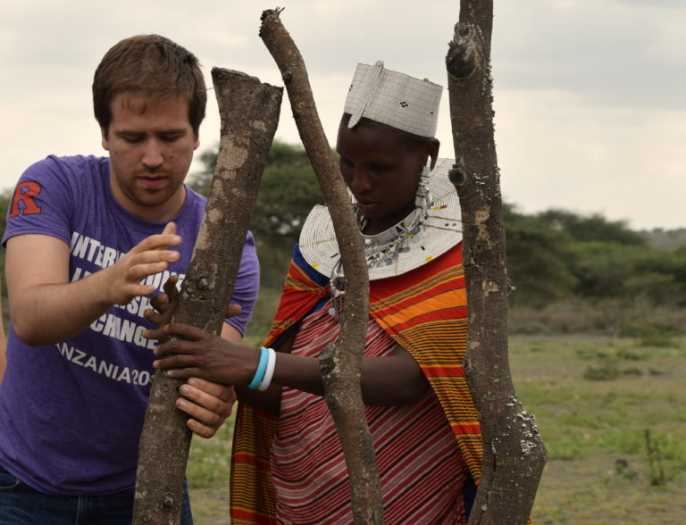 A Rutgers student aids a Tanzanian in their work