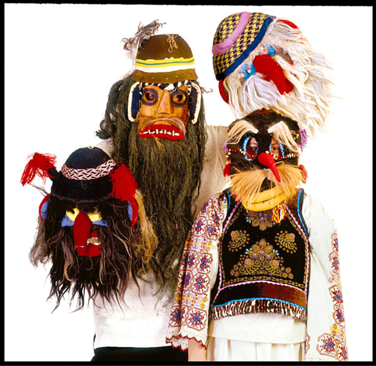 Photo of three figures in traditional Romanian masks