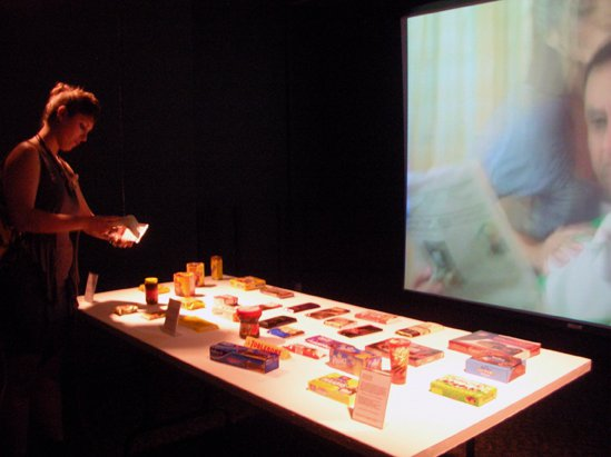 A women viewing a table covered with food items in a darkened room