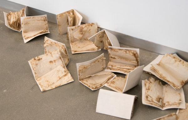 A group of books, yellowed with age, on a poured concrete floor