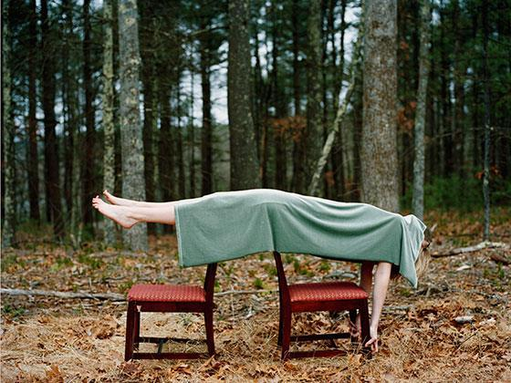 Body lying across two chairs, draped in a green blanket, in a woodland setting