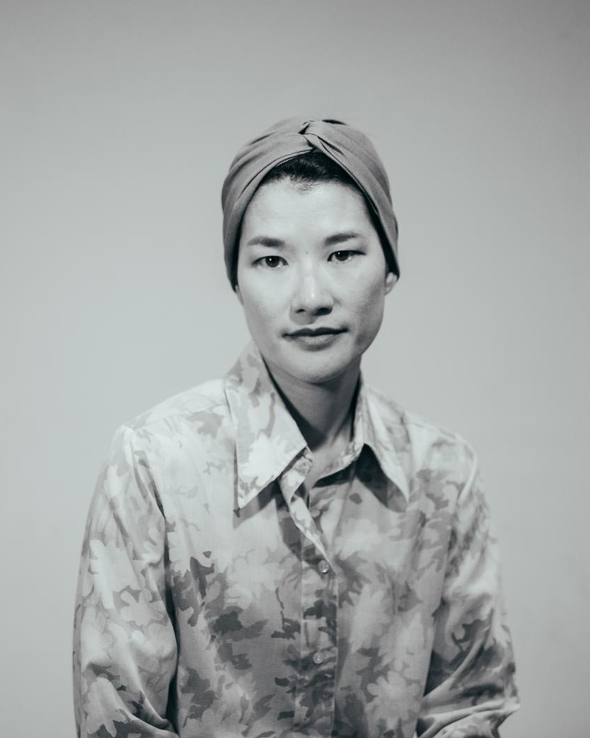 Black and white medium shot of an Asian woman wearing a floral shirt and head wrap.