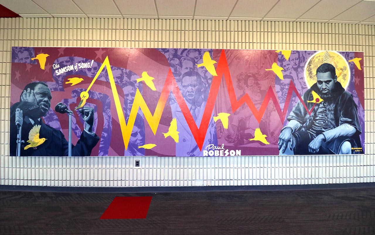 Mural depicting different moments in the life of Paul Robeson in shades of purple and maroon