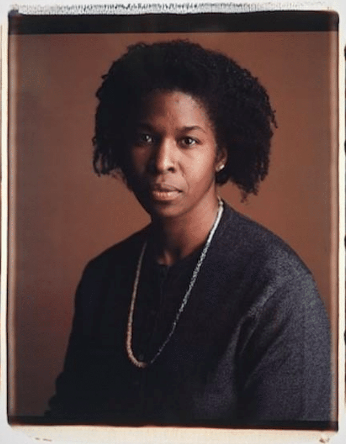 Portrait of black woman wearing a grey top and gold chain necklace