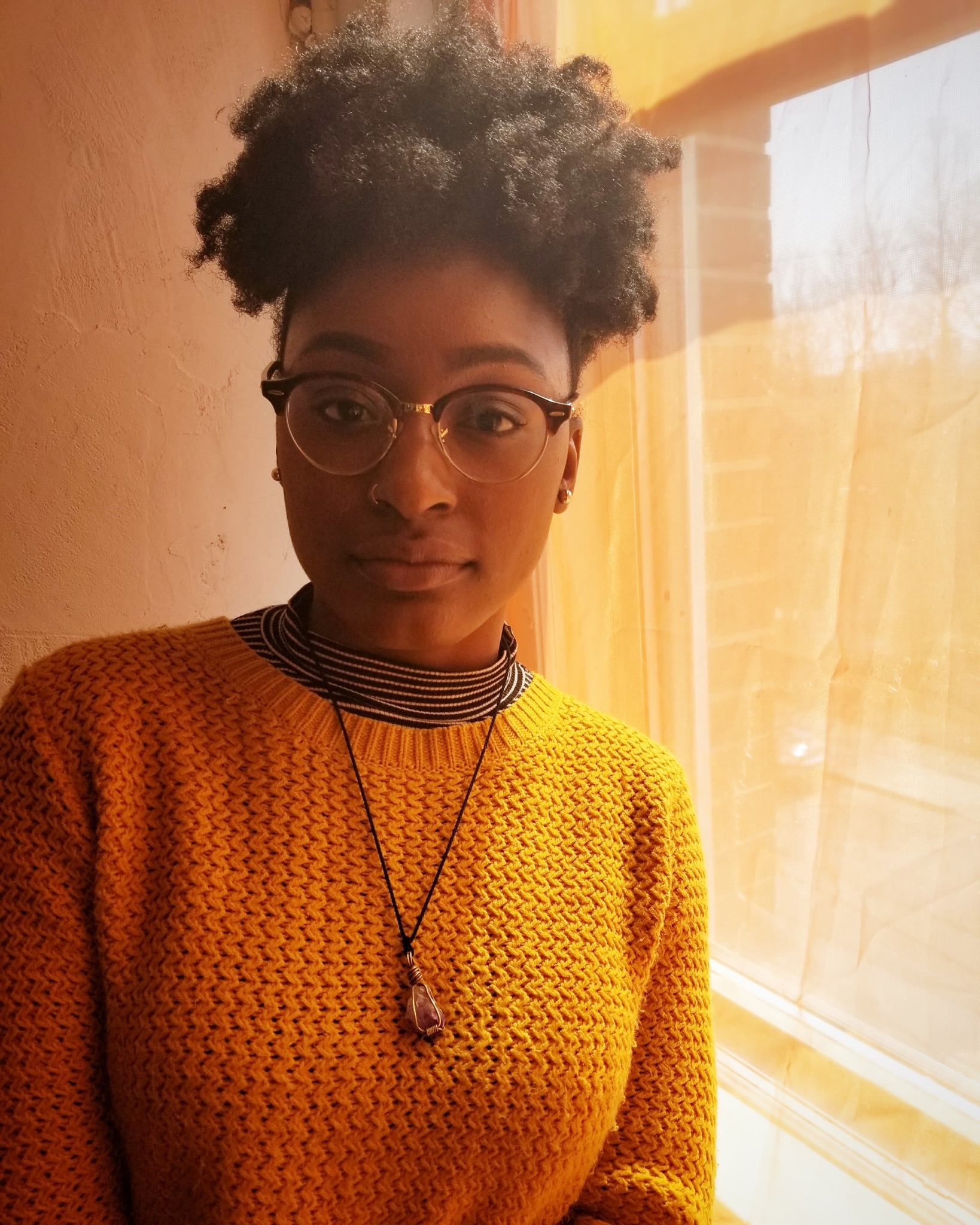 color photograph, headshot of Anika Carter in a yellow sweater leaning on a window and staring straight into the camera