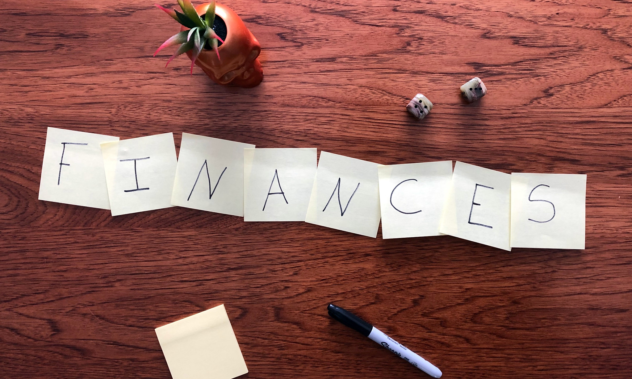 "A wood desk with Post-It notes spelling out the word, ""finances."""
