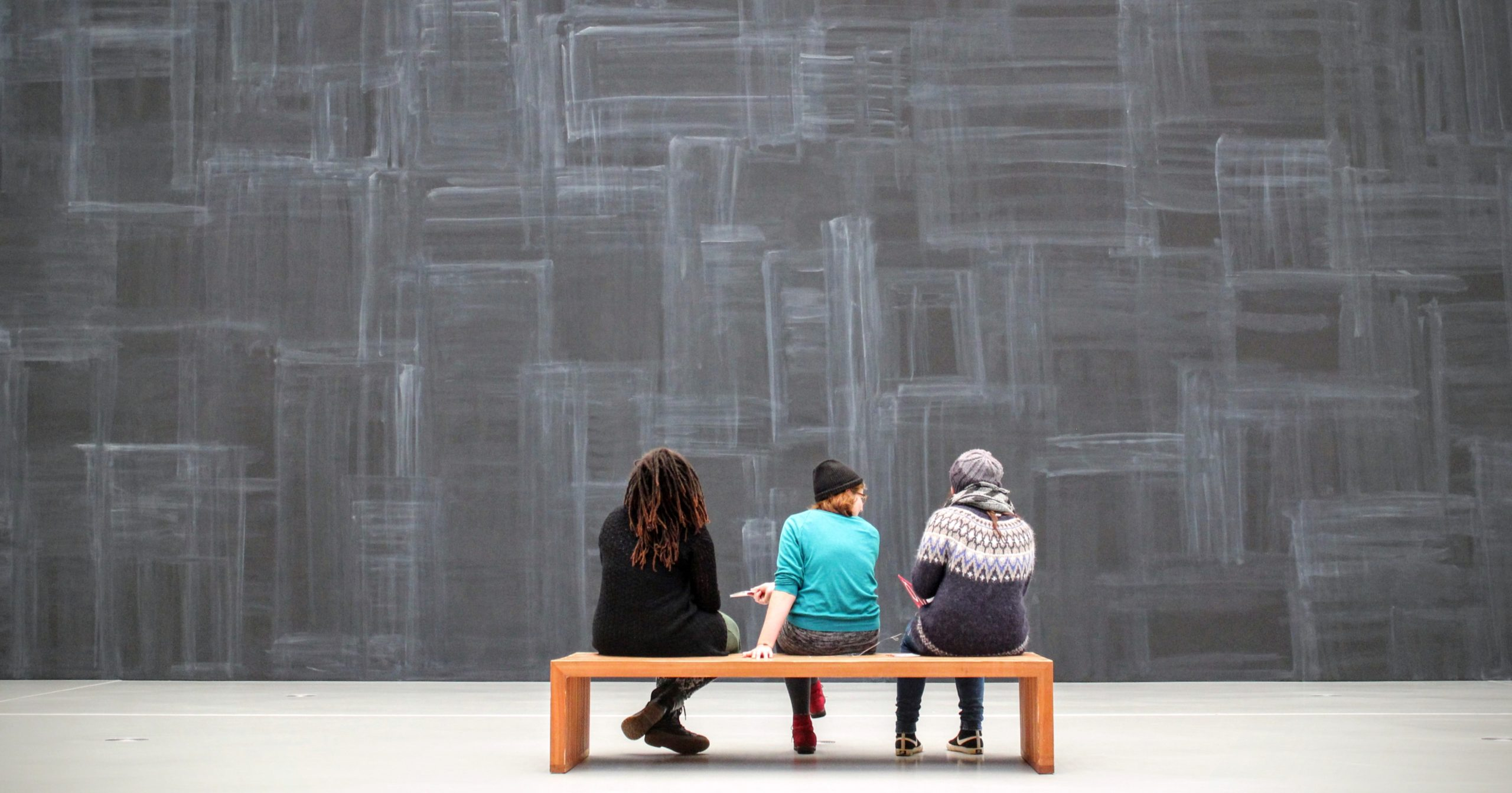 Three people site with their backs to the camera, looking at an art installation