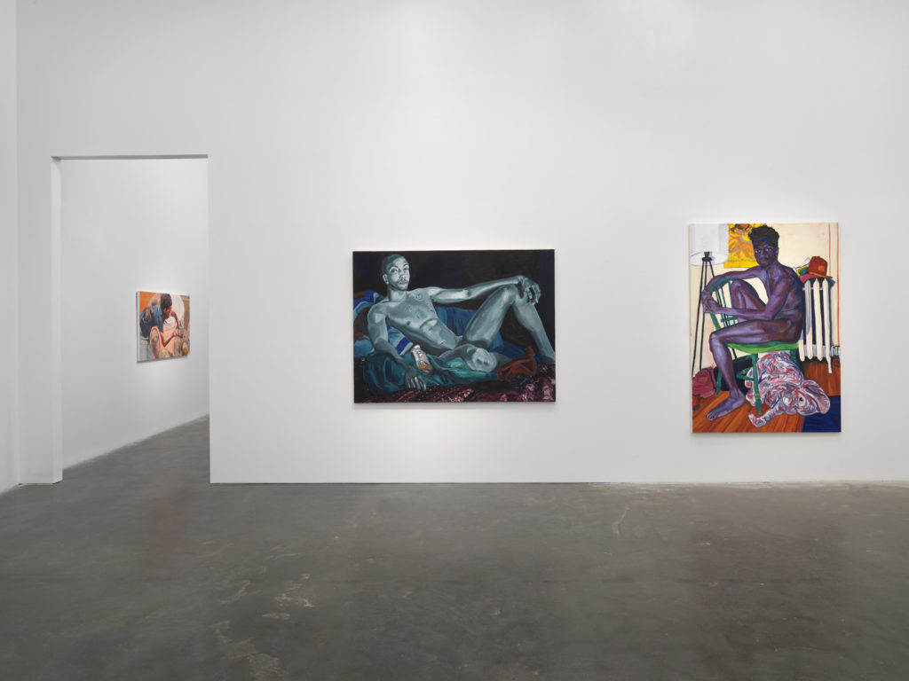 An installation view of an exhibition, with two paintings on a wall and a third visible through a doorway
