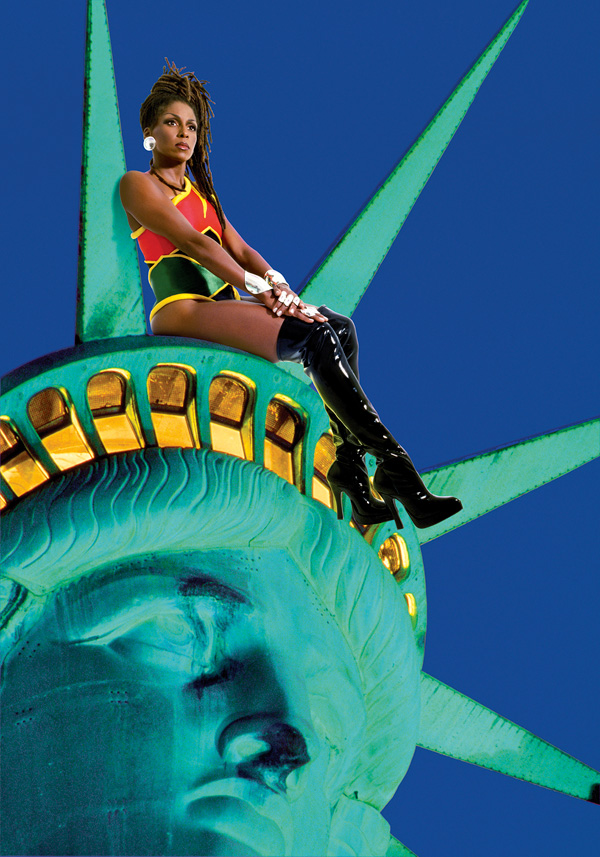 A Black woman in a super hero outfit sits on the statue of liberty's crown