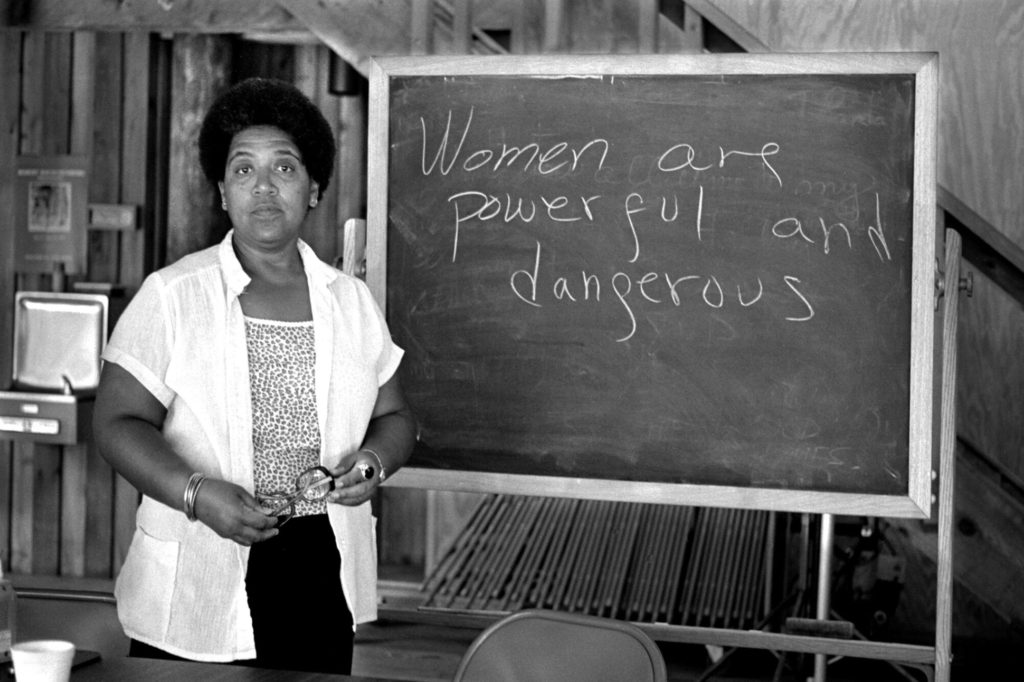 "A Black woman stands next to a chalk board that reads, ""Women are powerful and dangerous."""