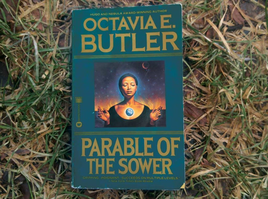 """A book lies on the grass. The book covers shows a black woman with her eyes closed, a small globe of light floating in from of her chest. The title of the book is """"Parable of the Sower"""" and its author is Octavia E. Butler."""