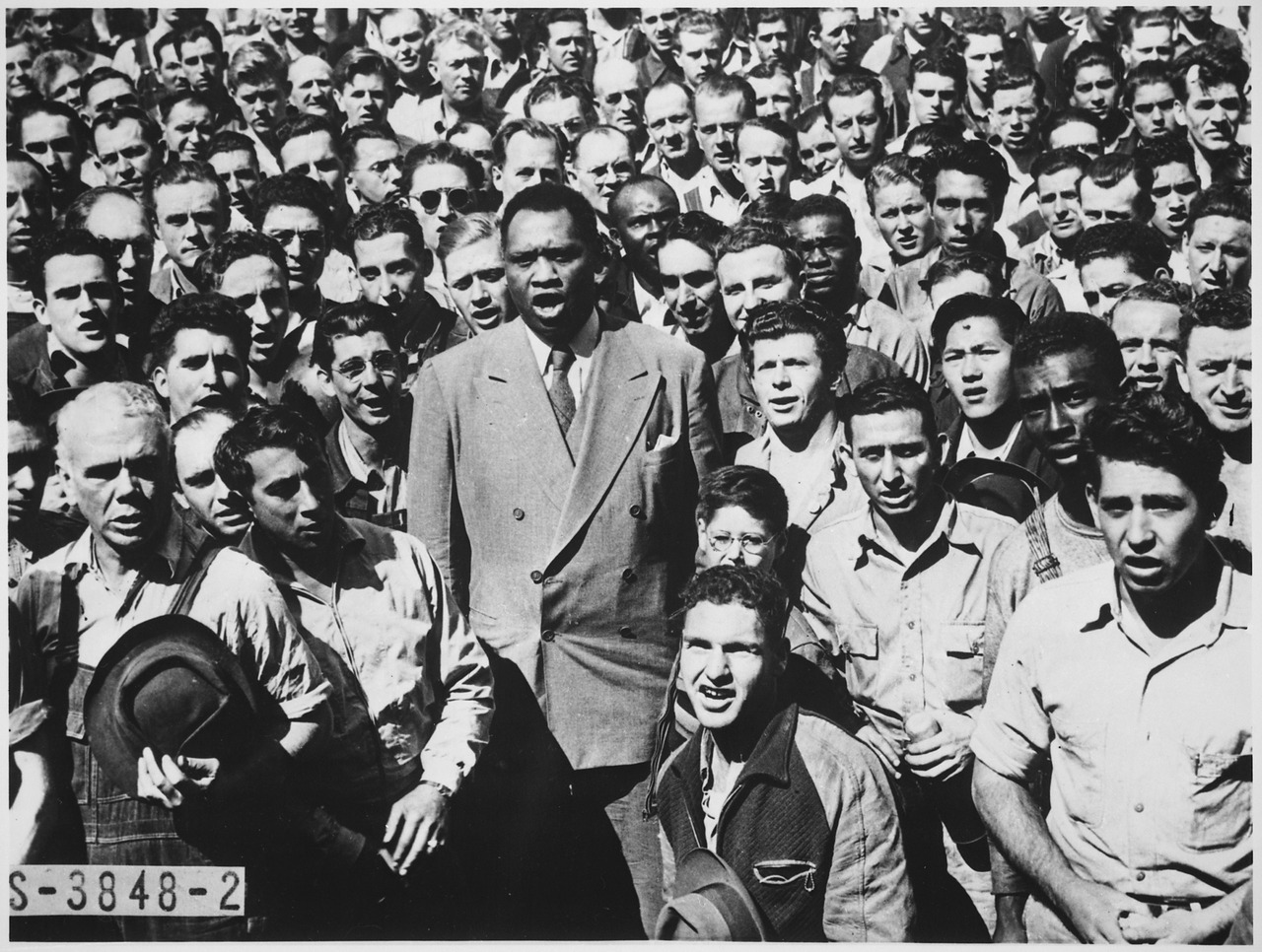 A Black man stands in the middle of a crowd, leading it in song