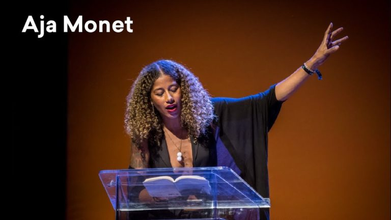 A black woman stands behind a podium, reading from a book.