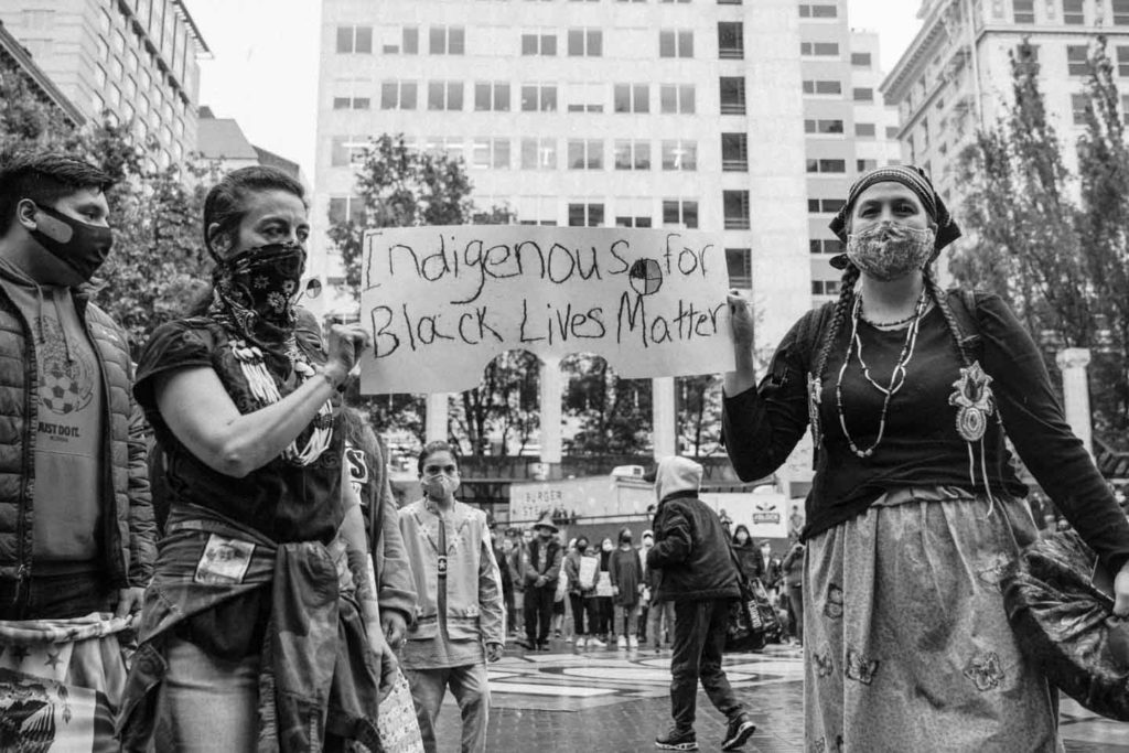 """Two people at a protest hold a sign that reads, """"Indigenous for Black Lives Matter."""""""