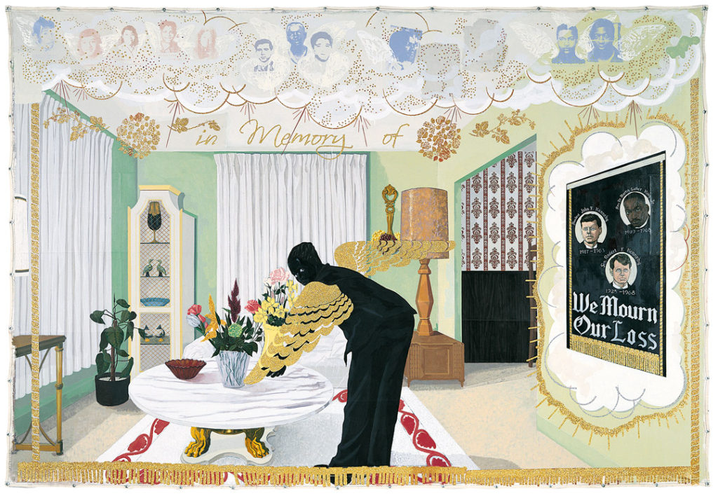 A Black figure with gold wings in a living room like setting bends over a table. Notably, there is a poster on the wall commemorating the lives of JFK, RFK, and Dr. Martin Luther King, Jr.