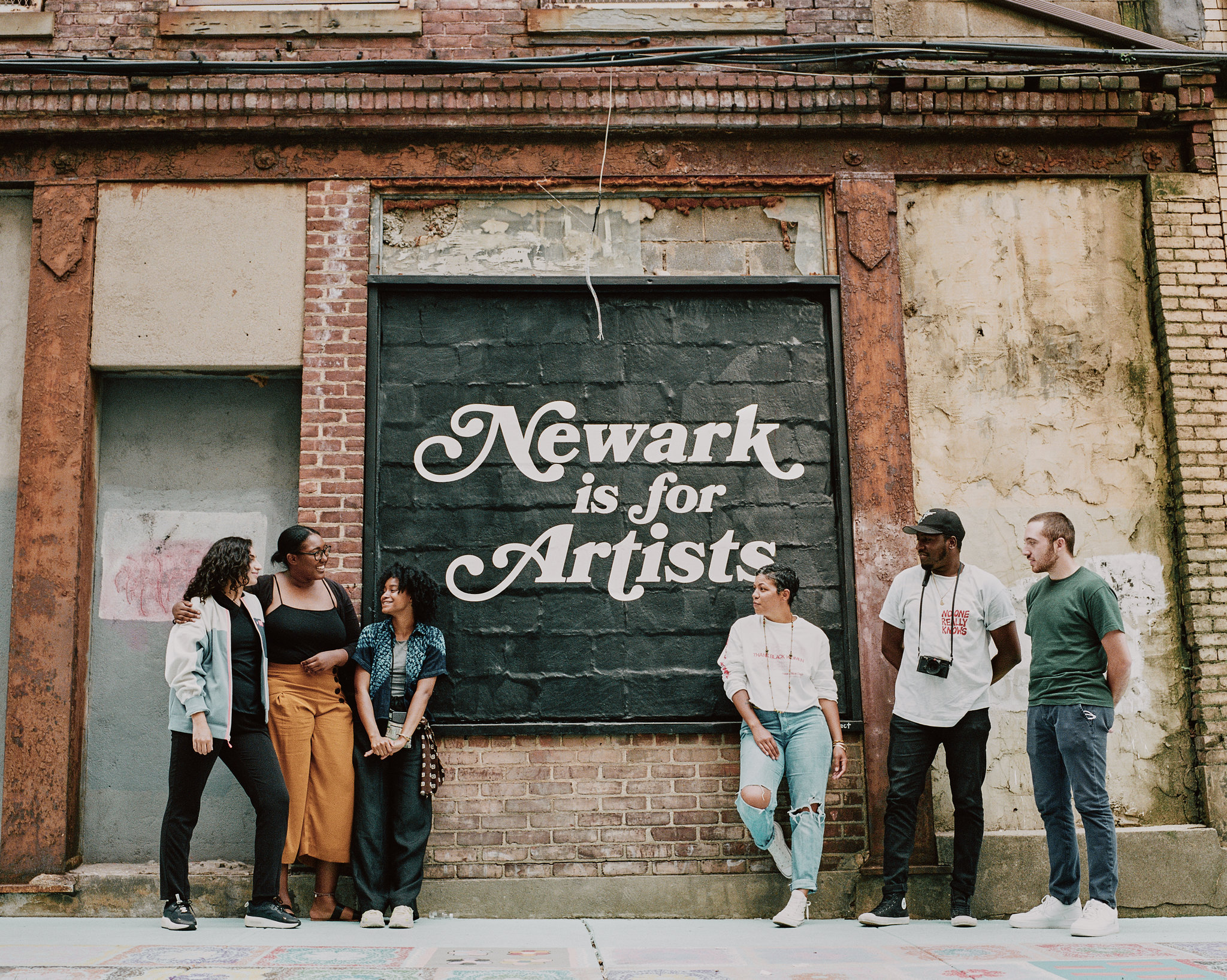 "A group of people stand outside, in front of a mural that reads, ""Newark is for Artists"""