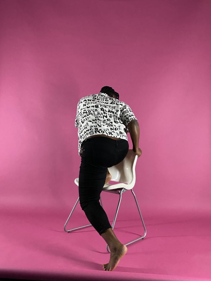 A Black woman, turned away from the viewer, climbs a white chair in front of a pink backdrop.