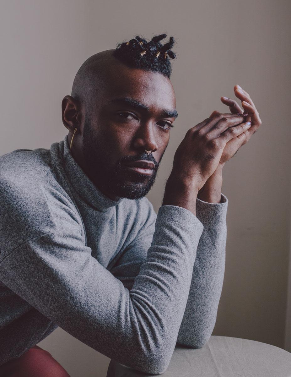 Medium shot of a young black man against a grey backdrop